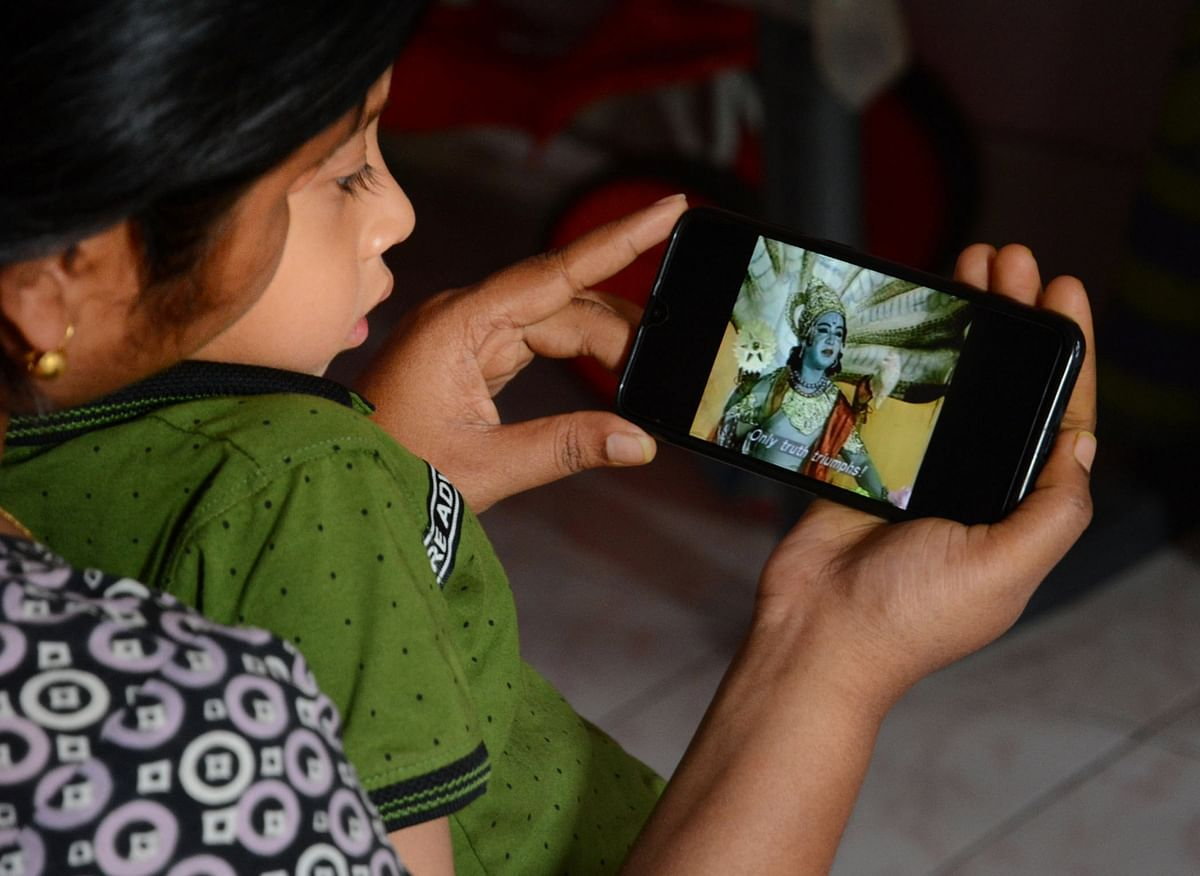 A young girl watches Ramayana on her phone, during the lockdown, in Guwahati, on March 28, 2020. (Photograph: PTI)