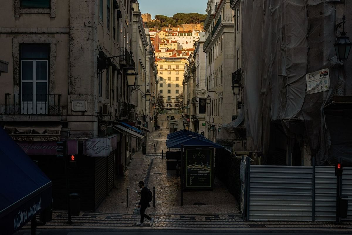 A pedestrian crosses a deserted street of usually crowded shops and cafes on March 22. (Photographer: Jose Sarmento Matos/Bloomberg)