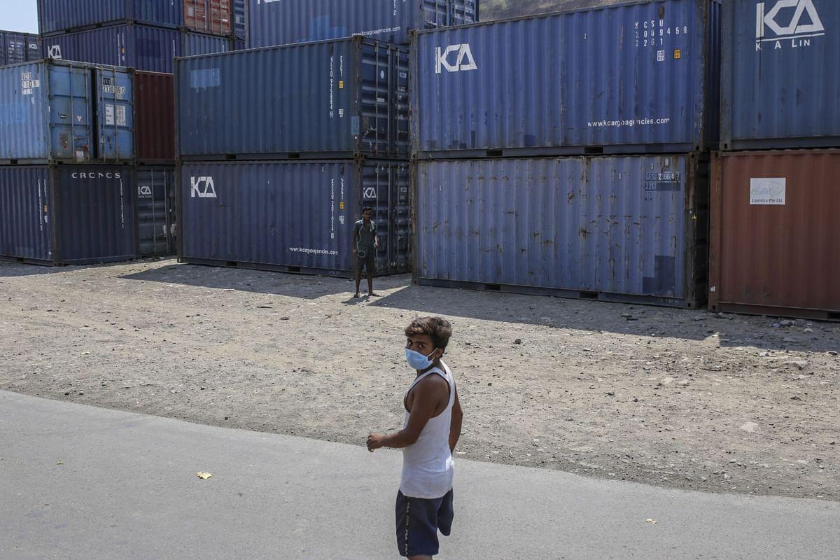 A man wearing a protective mask walks past shipping containers at the Jawaharlal Nehru Port, operated by Jawaharlal Nehru Port Trust (JNPT), in Navi Mumbai, Maharashtra, India. (Photographer: Dhiraj Singh/Bloomberg)