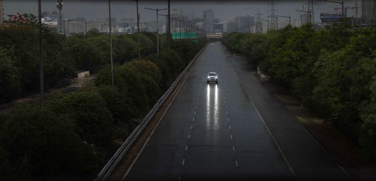 A car on the deserted Greater Noida Expressway during rainfall, in Noida on Sunday. (Photo: PTI)
