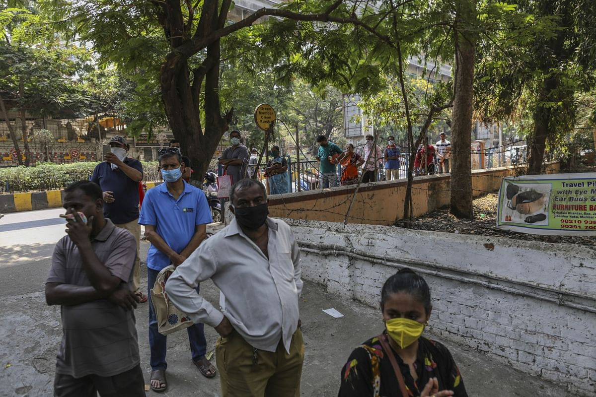 Customers wearing protective face masks form a queue for supplies outside supermarket in Mumbai, India. (Photographer: Dhiraj Singh/Bloomberg)