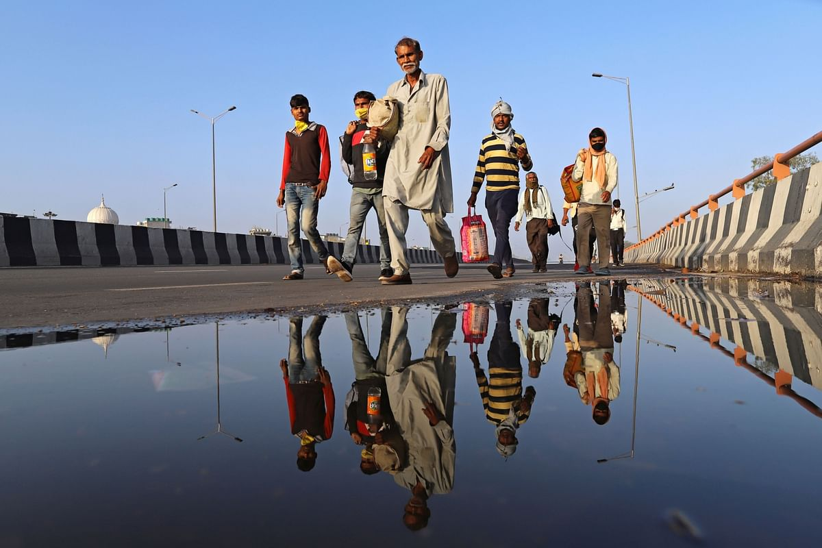 Migrant workers and their families walk along a road during a lockdown imposed due to the coronavirus in New Delhi, on  March 28, 2020. (Photographer: Anindito Mukherjee/Bloomberg)