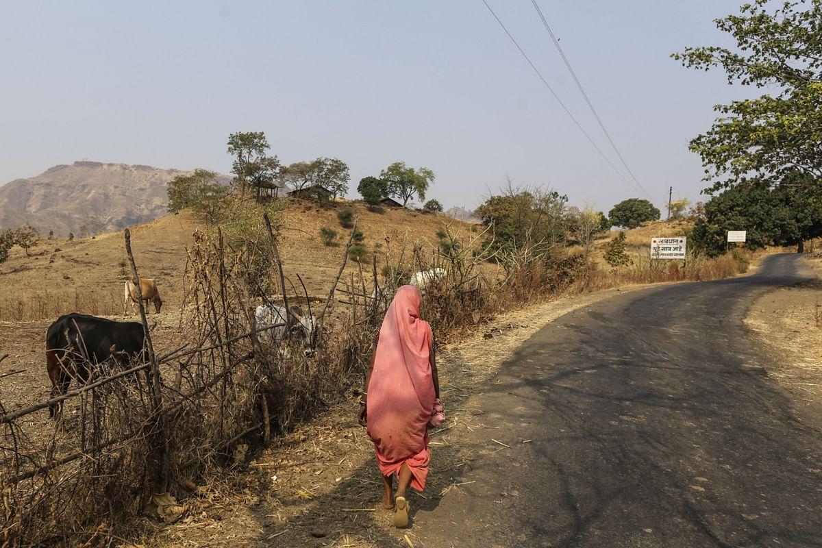 A woman walks along a road in Nadurbar district, Maharashtra. (Photographer: Dhiraj Singh/Bloomberg)