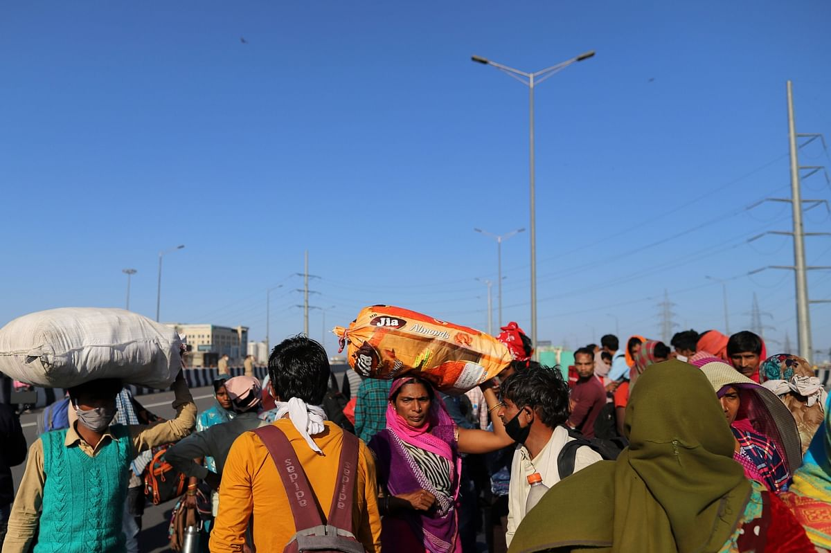 Migrant workers and their families that were unable to catch buses gather on NH-24 during a lockdown imposed due to the coronavirus on the outskirts of Delhi, India. (Photographer: Anindito Mukherjee/Bloomberg)