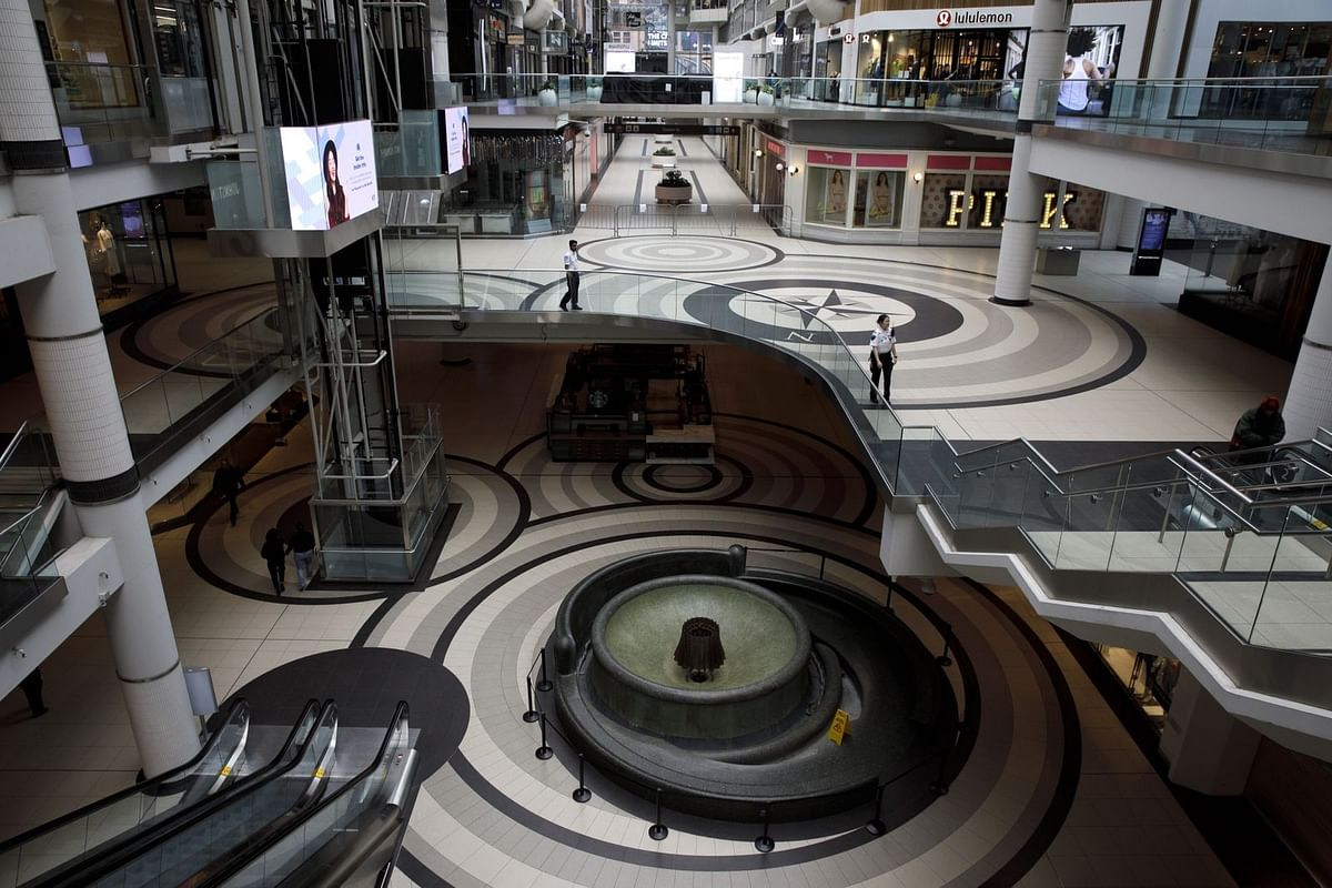 Security guards are among the few people inside the Toronto Eaton Centre on March 25. (Photographer: Cole Burston/Bloomberg)