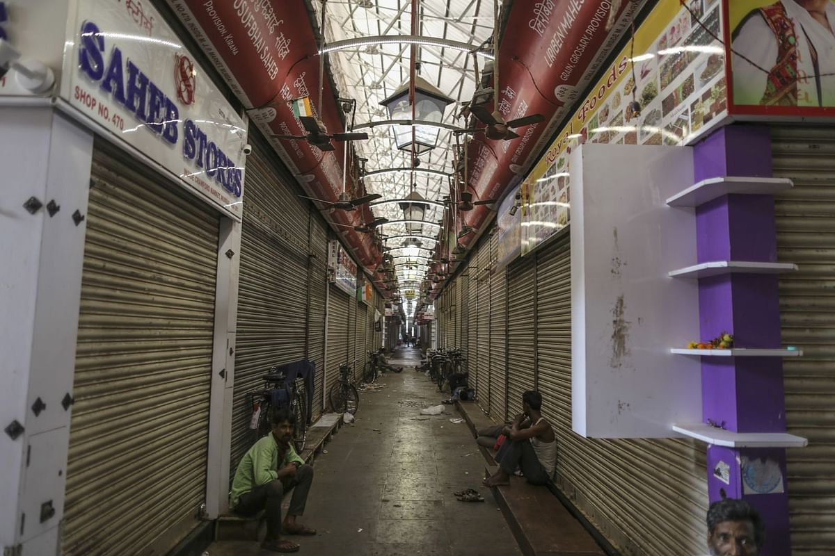 Men sit inside the closed Crawford Market on March 25. (Photographer: Dhiraj Singh/Bloomberg)