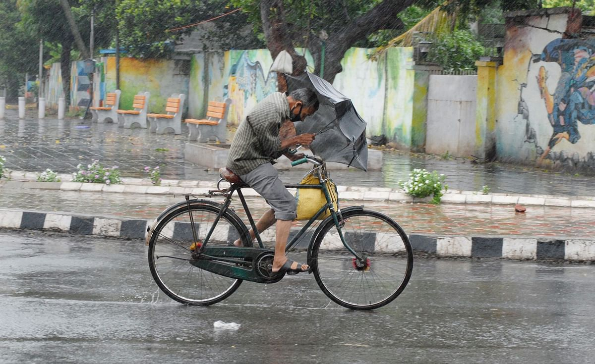 Man uses to protect himself from gusts of wind. (Source: PTI)