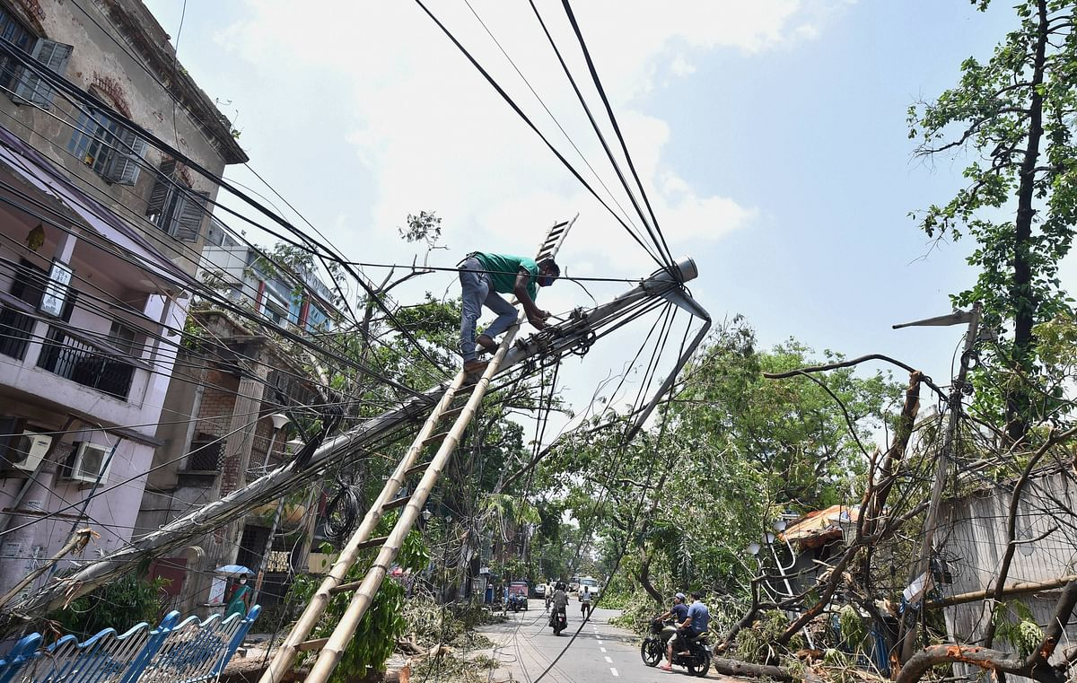 An electricity technician works on an electricity pole in Kolkata after the destruction from cyclone Amphan. (Source: PTI)