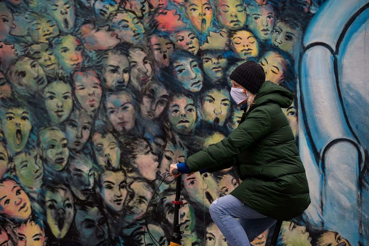 A cyclist wearing a protective face mask passes the Berlin Wall East Side Gallery, on Monday, April 13, 2020. (Photographer: Krisztian Bocsi/Bloomberg)