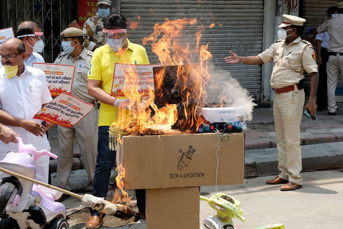 Protesters burn an image of Chinese President Xi Jinping at a demonstration. (Photographer. T. Narayan/Bloomberg)