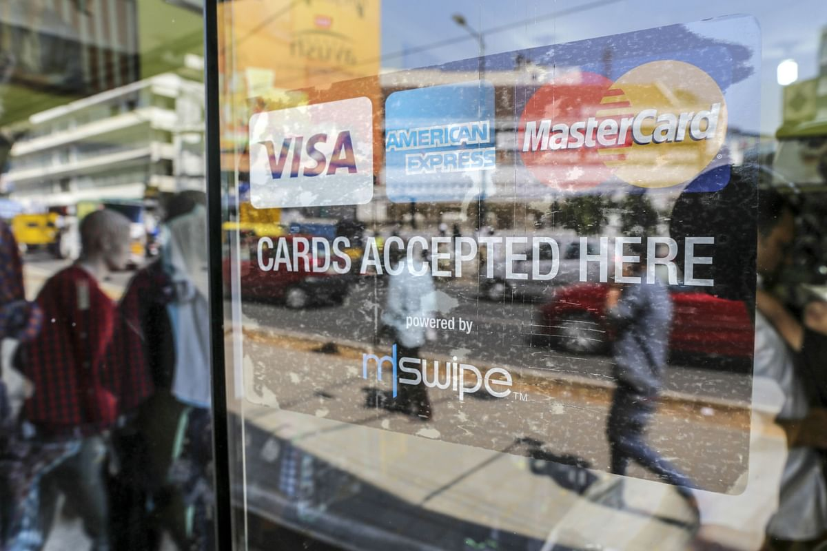 A sign showing logos of various electronic payment methods is displayed on the window of a s store in Bengaluru. (Photographer: Dhiraj Singh/Bloomberg)
