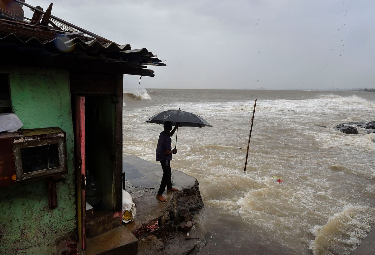 A man stands near a shanty built on the edge of the Arabian Sea at Bandra. (Source: PTI)