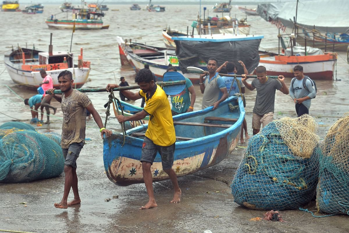 Fishermen pull a boat as they move to a safer place after Cyclone Nisarga made landfall, at Uttam in Thane. (Source: PTI)