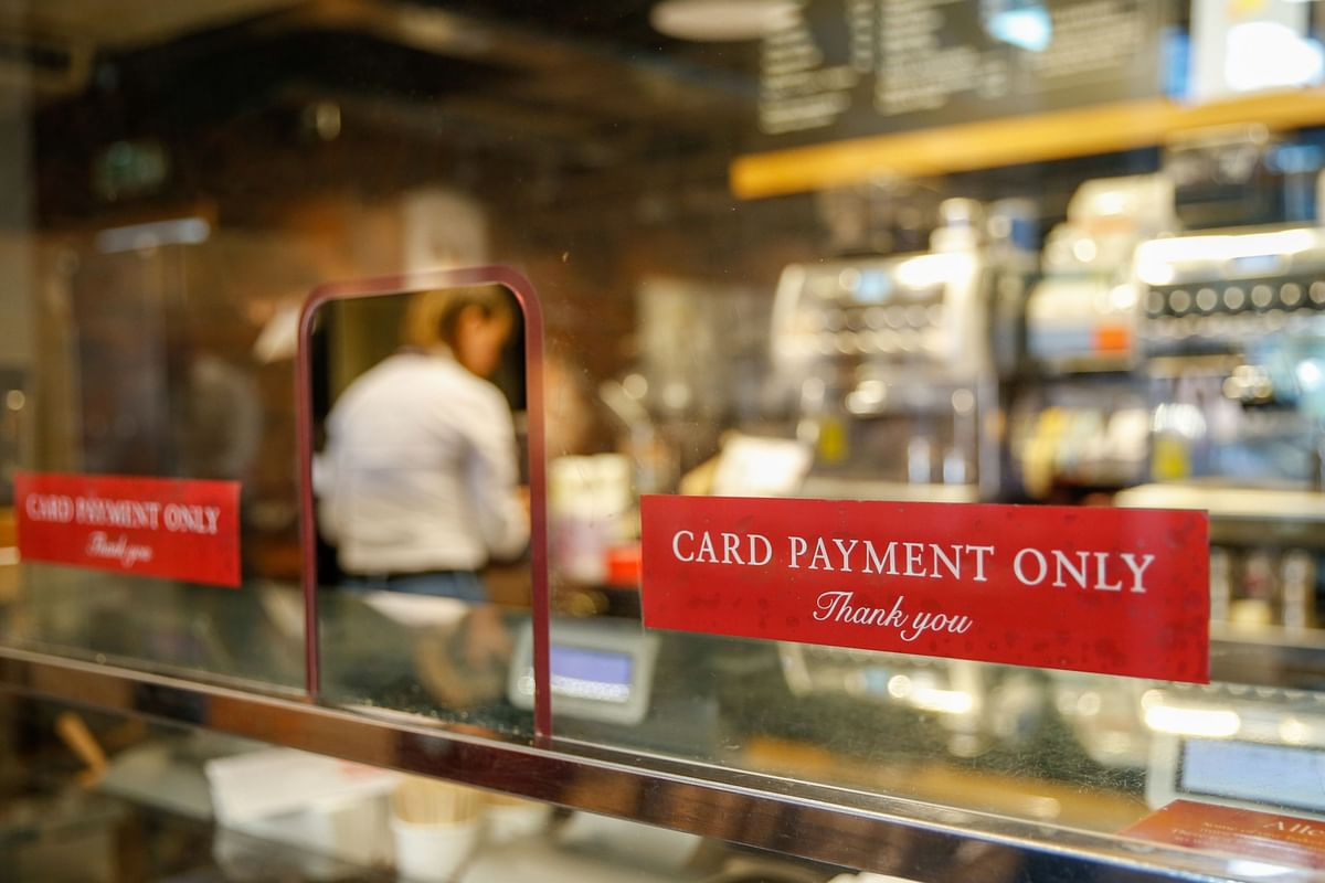 Card payment only notices sit on a protective screen in London. (Photographer: Hollie Adams/Bloomberg)