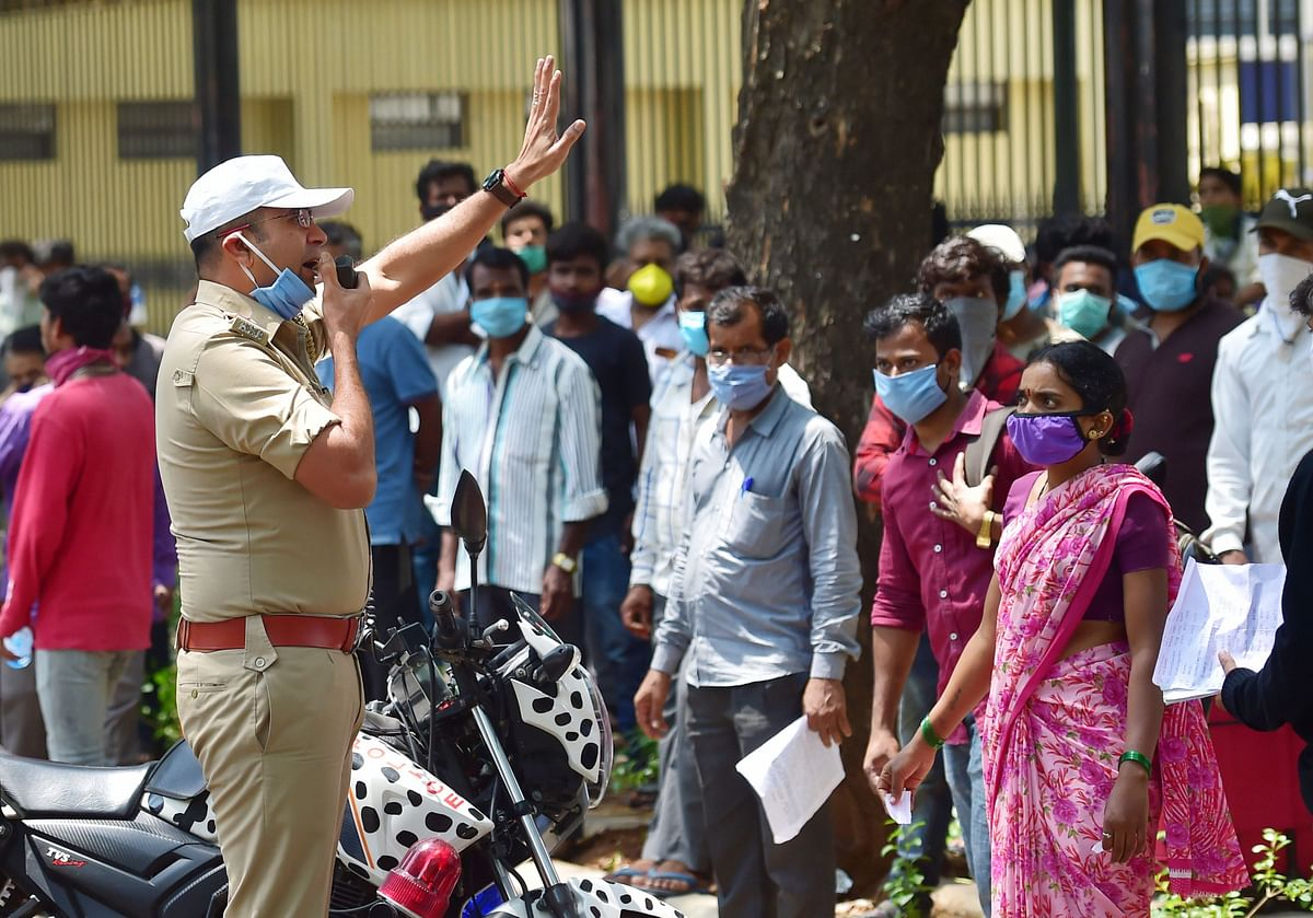 A police inspector appeals migrant workers to respect social distancing guidelines,  in Bengaluru, on May 1, 2020. (Photograph: PTI