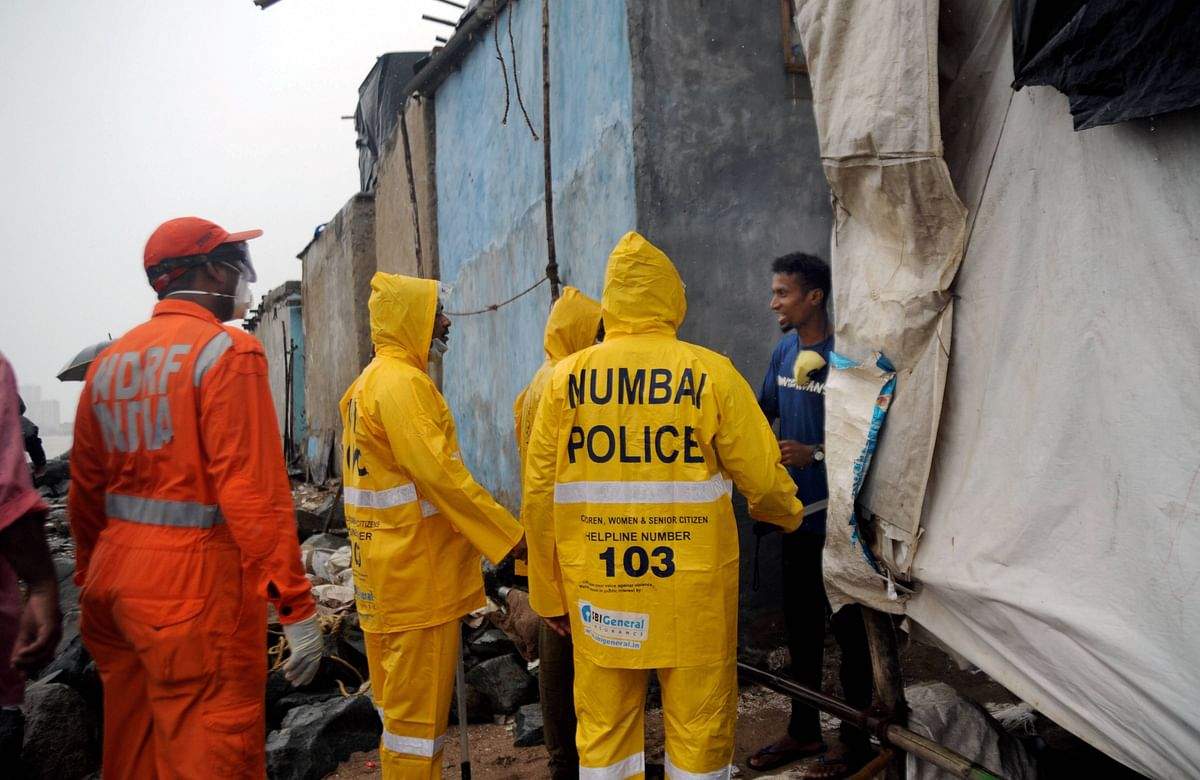 National Disaster Response Force personnel along with Mumbai police evacuate people living along Versova beach. (PTI)