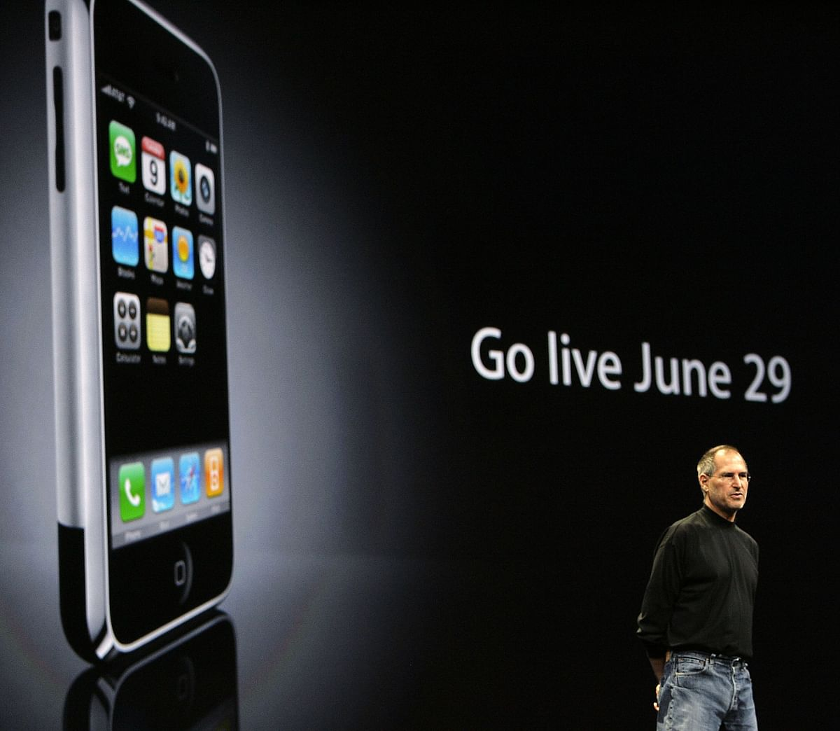 Steve Jobs speaks in front of a projection of the first iPhone ahead of its launch, in San Francisco, California, on June 11, 2007. (Photographer: Tony Avelar/Bloomberg News)