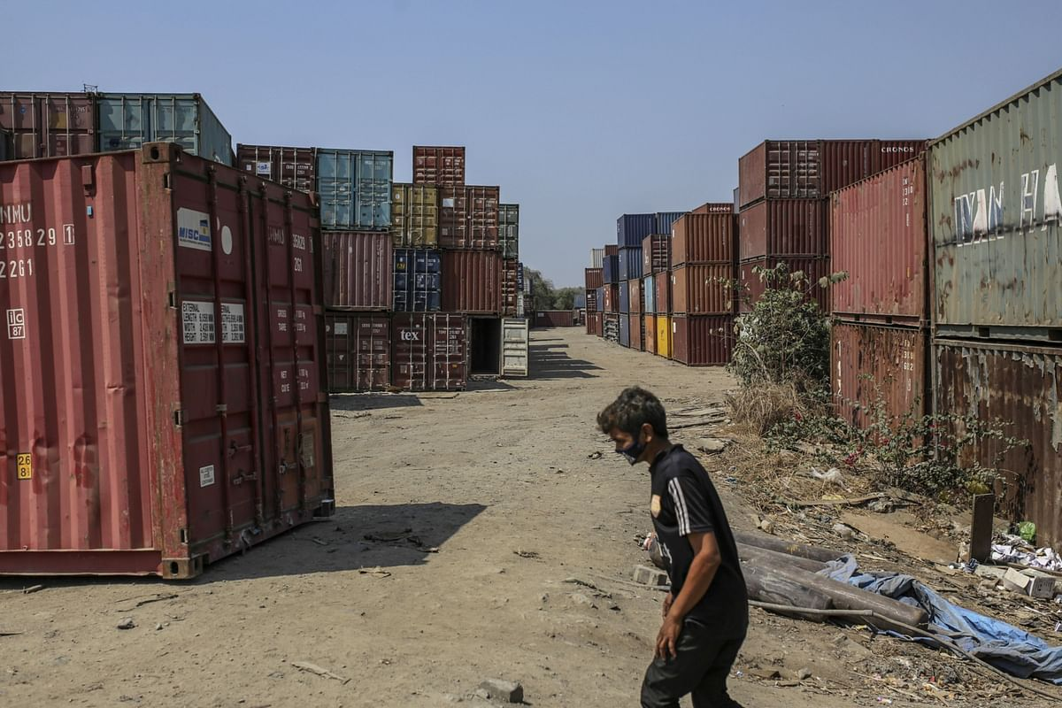 A worker in a mask crosses shipping containers JNPT, in Navi Mumbai, on March 30, 2020. (Photographer: Dhiraj Singh/Bloomberg)