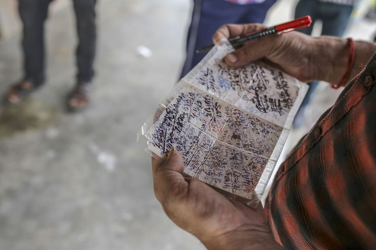 An official holds a handwritten note of distributed rations at a state-run store in a village in Tikamgarh district, Madhya Pradesh on Aug. 7, 2020. (Photographer: Dhiraj Singh/Bloomberg)