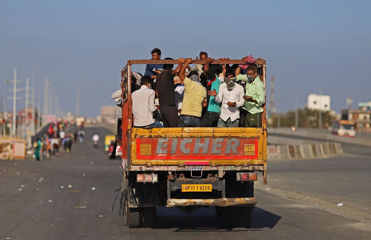 Migrant workers and their families ride on a truck during a lockdown (Photographer: Anindito Mukherjee/Bloomberg)