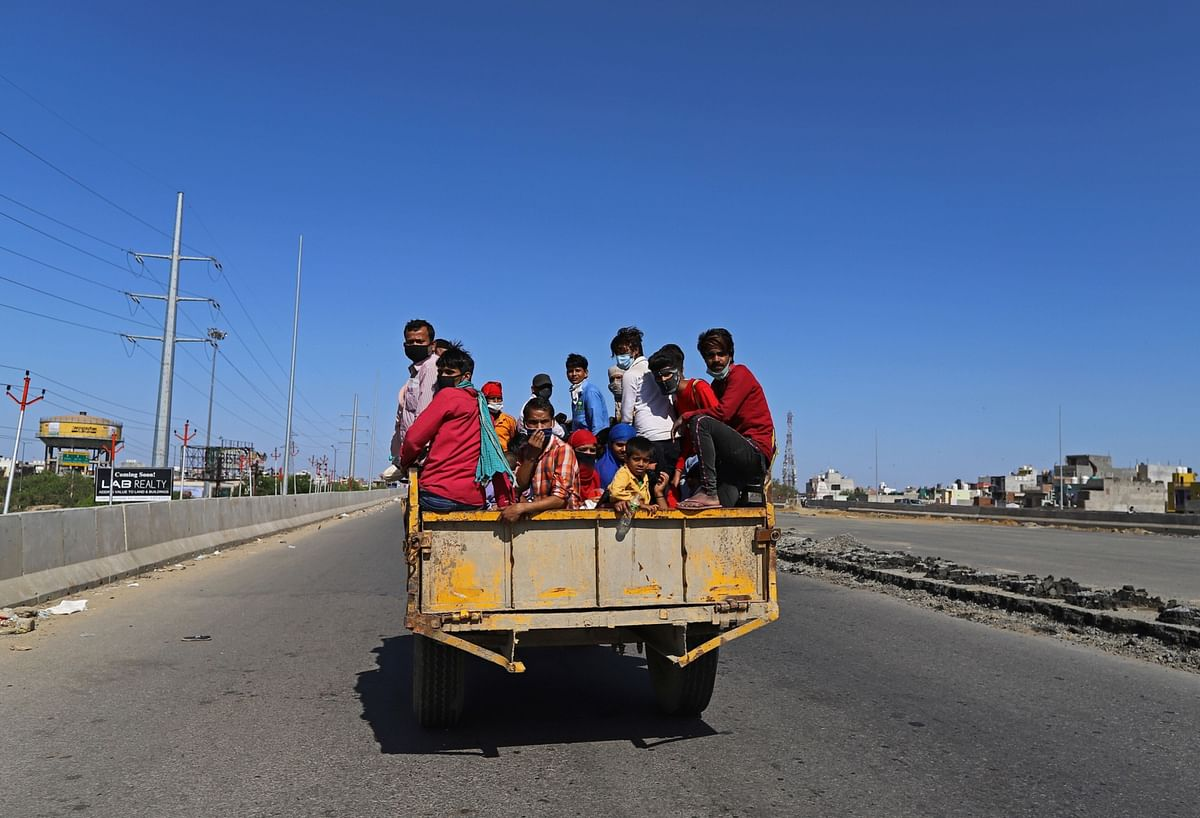 Migrant workers and their families sit in the back of a truck traveling along National Highway 24 during a lockdown (Photographer: Anindito Mukherjee/Bloomberg)
