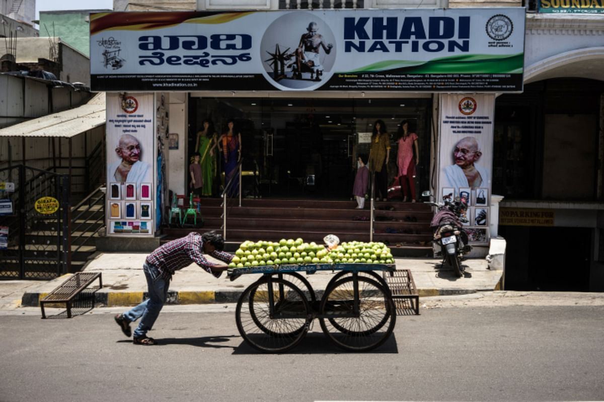 A fruit vendor pushes a cart past the Khadi Nation store in the Malleswaram locality of Bengaluru. (Photograph: Sanjit Das/Bloomberg)