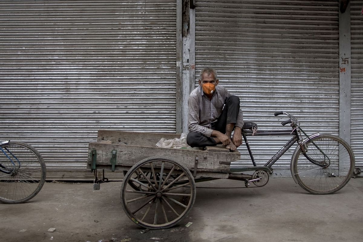 A day laborer  sits on a tricycle outside a shuttered store in New Delhi, on Aug. 31, 2020. (Photographer: Anindito Mukherjee/Bloomberg)