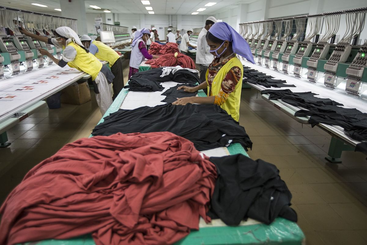 Workers embroider t-shirts with logos on the production line of a garment factory in Gazipur, Bangladesh, on May 30, 2013. (Photographer: Jeff Holt/Bloomberg)
