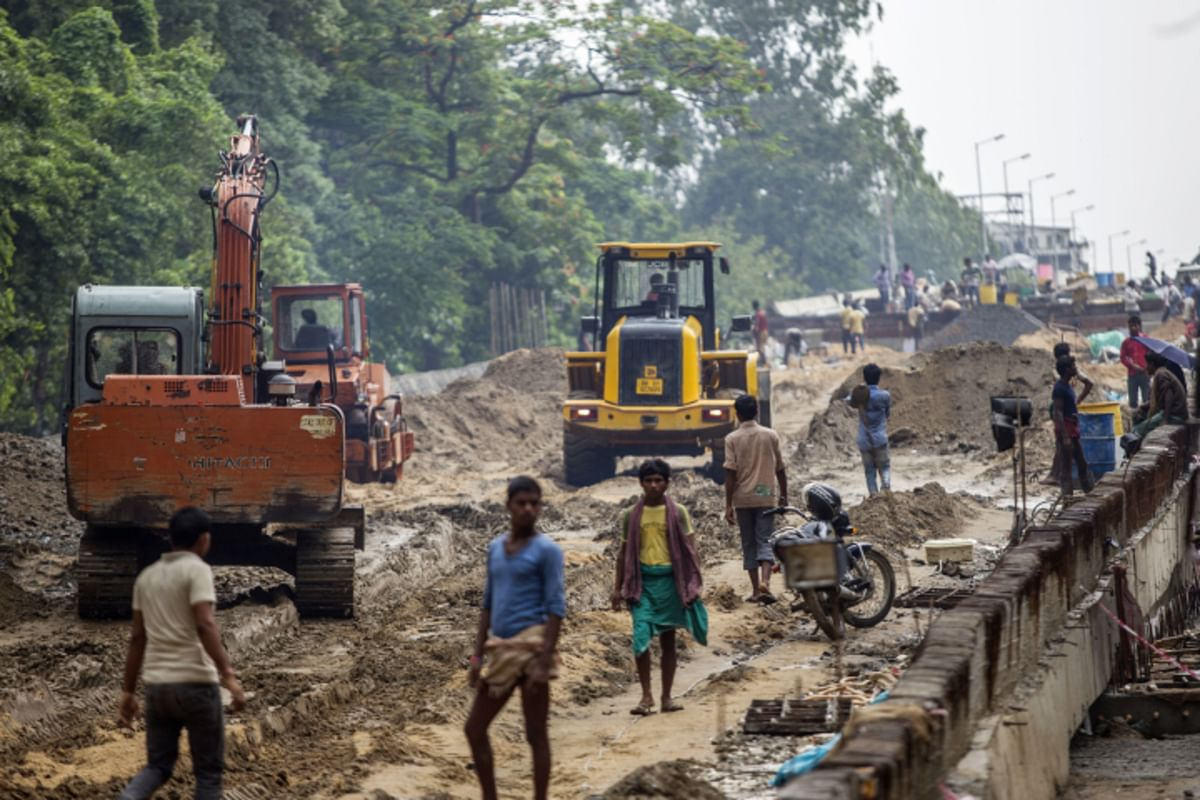 People walk through the construction site for an overpass in Patna, Bihar. (Photographer: Prashanth Vishwanathan/Bloomberg)