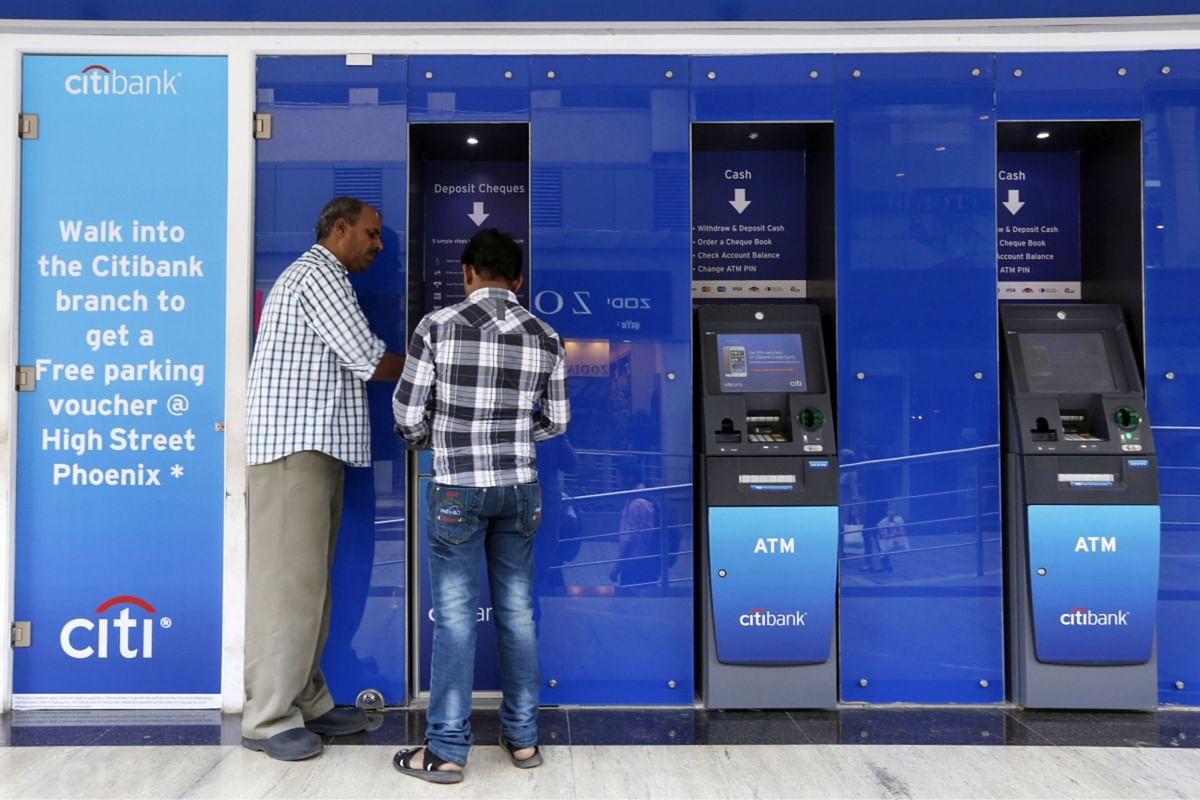 An employee assists a customer at an automated teller machine (ATM) at a Citigroup Inc. Citibank branch in Mumbai, India. (Photographer: Vivek Prakash/Bloomberg)