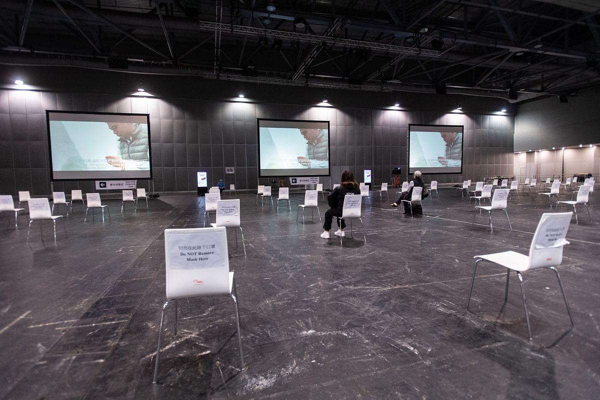 Travelers watch a saliva sample information video at a coronavirus testing facility at the AsiaWorld-Expo in Hong Kong on May 14. Photographer: Laurel Chor/Bloomberg