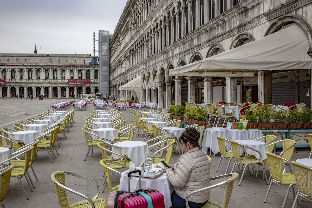 A lone diner in Venice's Piazza San Marco on March 5. As the pandemic accelerated through the year, the hospitality and food industries suffered grievous financial losses. Photographer: Francesca Volpi/Bloomberg