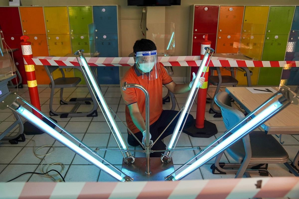 In West Java, Indonesia, a maintenance worker uses ultraviolet light to sanitize a classroom on July 24. Photographer: Dimas Ardian/Bloomberg