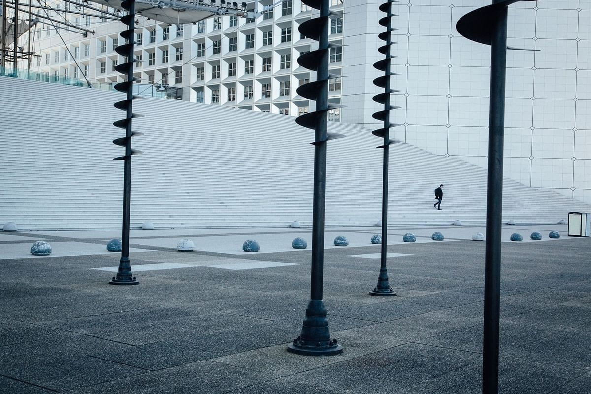 A pedestrian at La Defense's Grande Arche in Paris on March 24. Photographer: Cyril Marcilhacy/Bloomberg