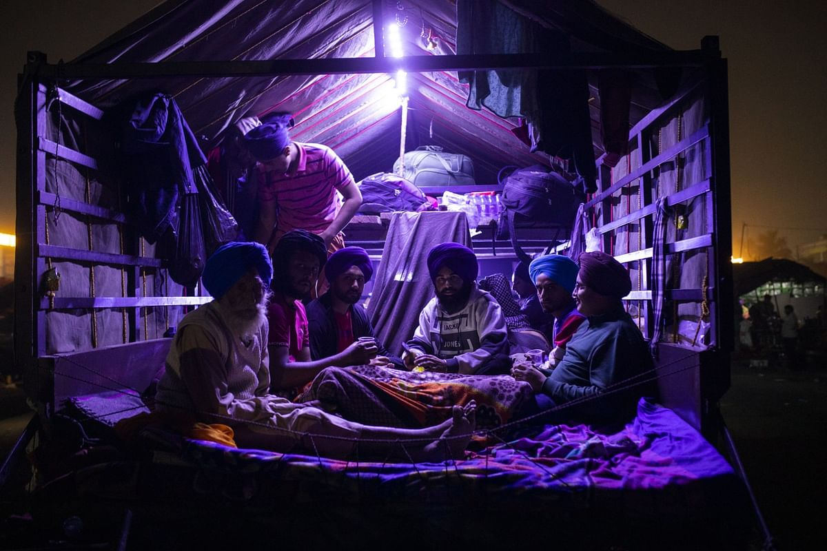 Farmers sit inside a tractor trailer at a protest site at a road block on the Delhi-Haryana border crossing in Singhu, Delhi, India. (Photographer: Prashanth Vishwanathan/Bloomberg)
