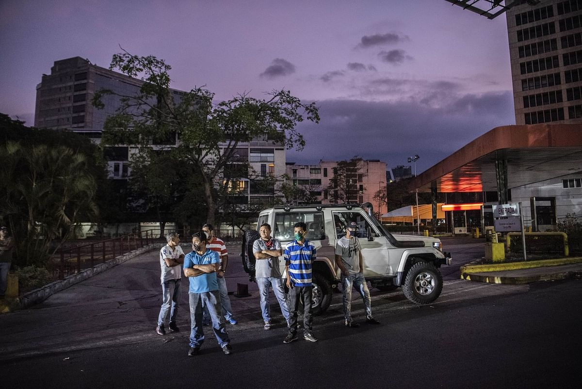 Drivers stand at a gas station in Caracas on May 26. Venezuelan President Nicolás Maduro had said fuel prices would increase starting in June. Photographer: Carlos Becerra/Bloomberg