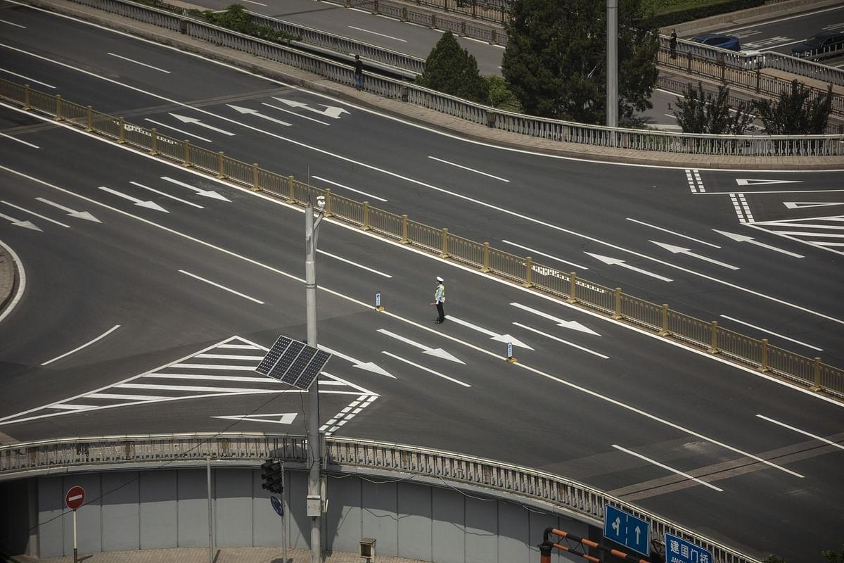 On a multilane road in Beijing on May 22, a traffic conductor had little to do. Photographer: Qilai Shen/Bloomberg