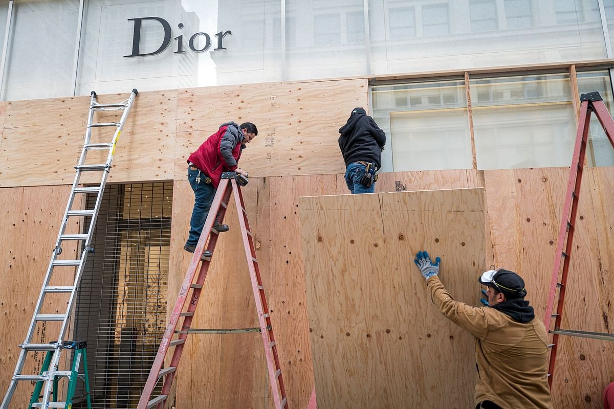 Workers board up the windows of a Christian Dior store in San Francisco on March 17 after people were ordered to stay home. Photographer: David Paul Morris/Bloomberg