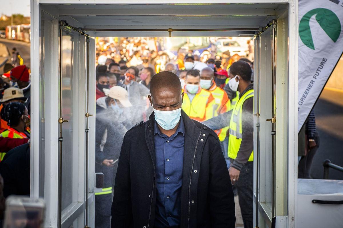 A commuter walks through a sanitization tunnel at the Rea-Vaya Thokoza Park bus station in Johannesburg on May 14. Photographer: Waldo Swiegers/Bloomberg