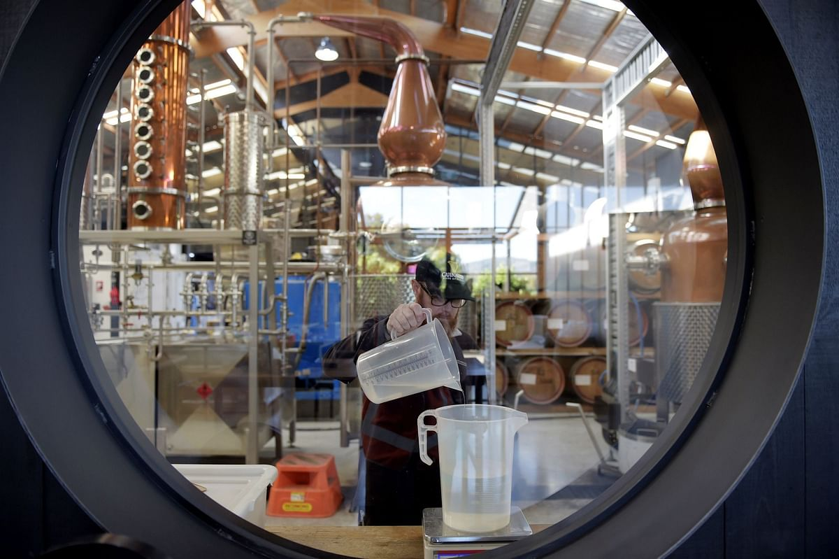 A man produces hand sanitizer at the Four Pillars Gin Distillery in Healesville, Australia, on April 1. Many industries retooled to help with shortages of protective equipment and disinfectant. Photographer: Carla Gottgens/Bloomberg