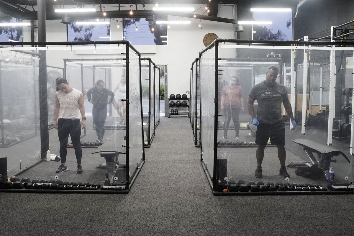 Gym members work out in social distancing pods at Inspire South Bay Fitness in Redondo Beach, California, on June 19. Like personal care salons, gyms have been crushed by the pandemic. Photographer: Bing Guan/Bloomberg
