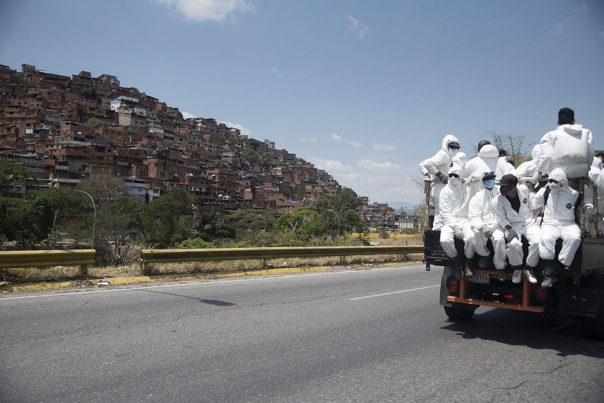 City workers in protective gear drive through Caracas on March 26. Venezuela is also facing a growing food insecurity crisis. Photographer: Carlos Becerra/Bloomberg