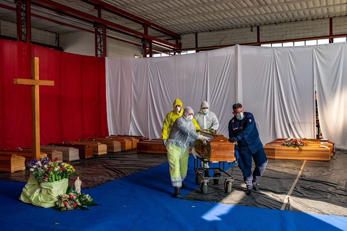 Civil protection members and police transport a coffin from a repurposed warehouse to a crematorium near Bergamo, Italy, on April 4. Photographer: Francesca Volpi/Blooomberg