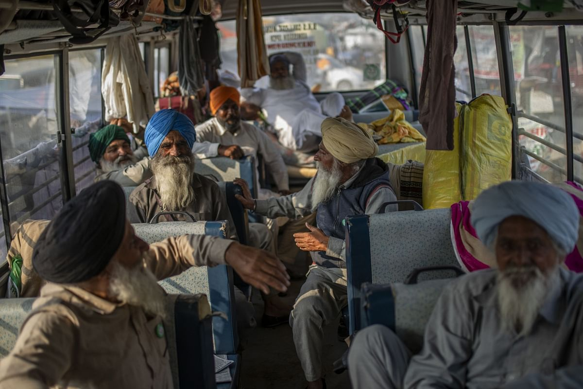 Farmers sit inside a bus at a protest site at a road block on the Delhi-Haryana border crossing in Singhu, Delhi, India. (Photographer: Prashanth Vishwanathan/Bloomberg)