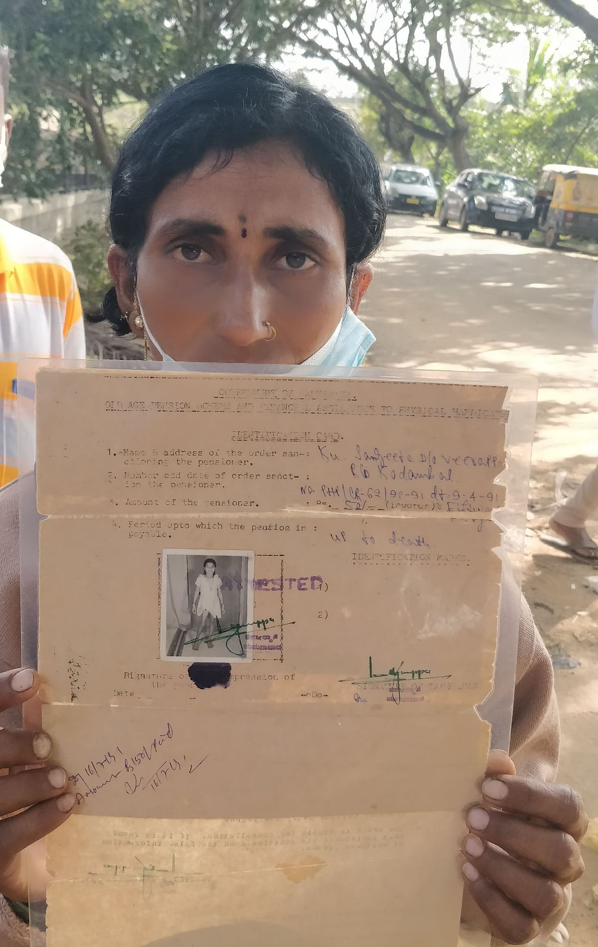 Manjula holds up her sister's disability card. (Source: Ashwini YS for BloombergQuint)