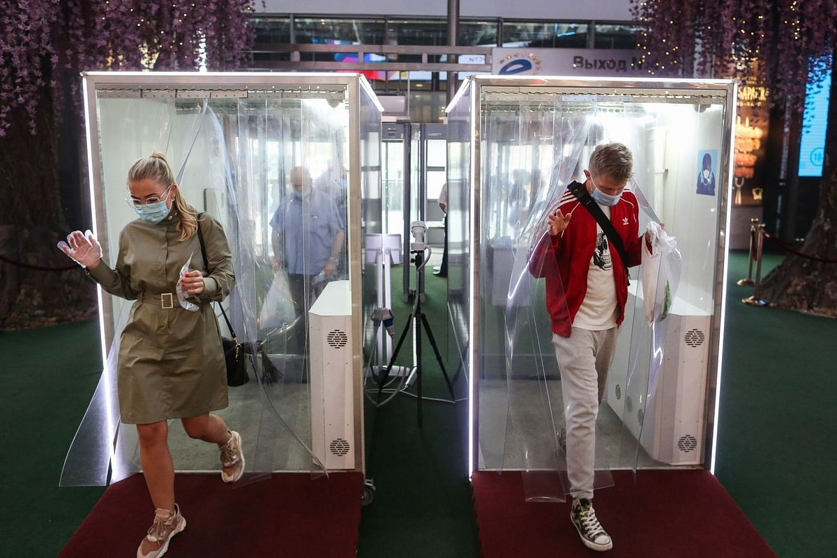 Shoppers pass through disinfection cabins at the Evropeysky Shopping Center in Moscow on Aug. 11. Photographer: Andrey Rudakov/Bloomberg