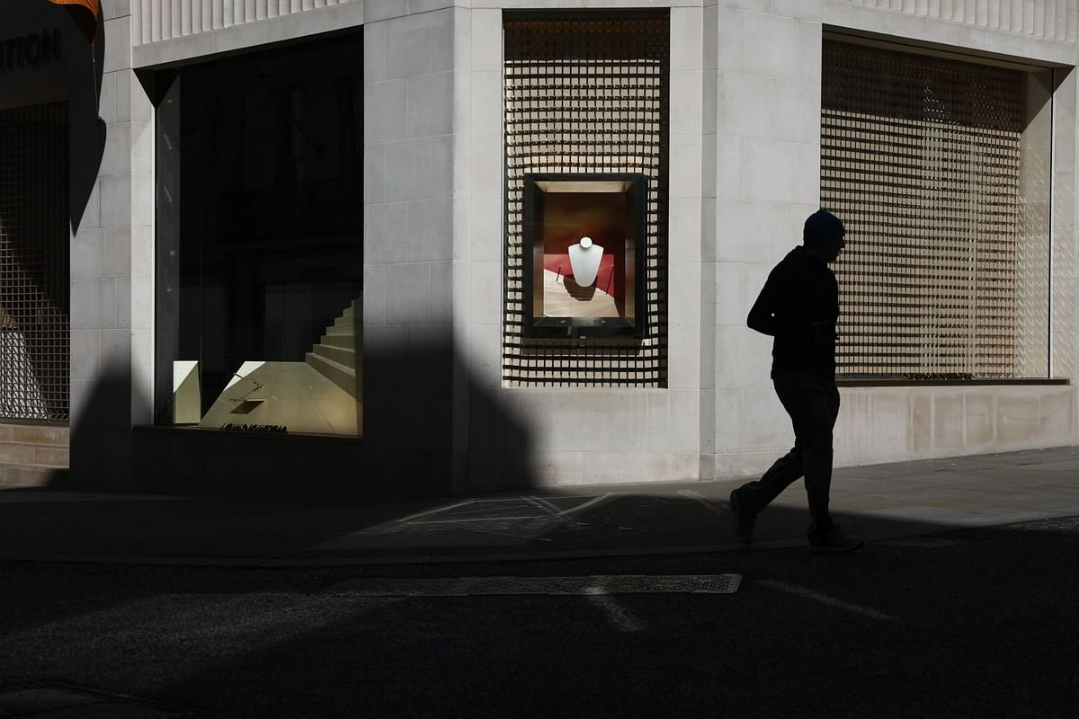In-store shopping halted as consumers turned to the internet to satisfy material needs. A pedestrian passes an empty display window at a closed Louis Vuitton store in London on March 24. Photographer: Simon Dawson/Bloomberg