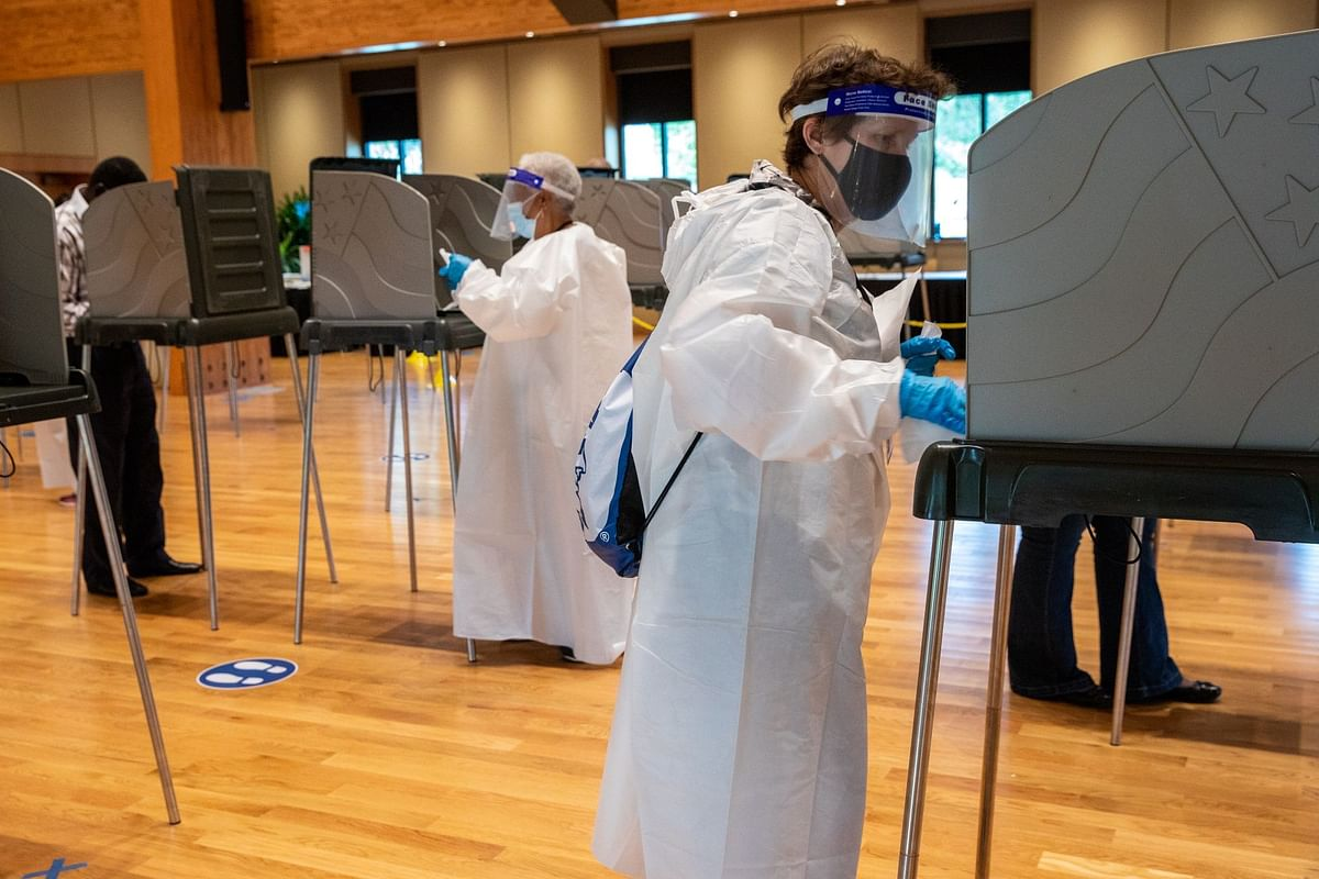 Election officials sanitize voting booths ahead of the U.S. presidential election in Durham, North Carolina, on Oct. 15. Photographer: Rachel Jessen/Bloomberg