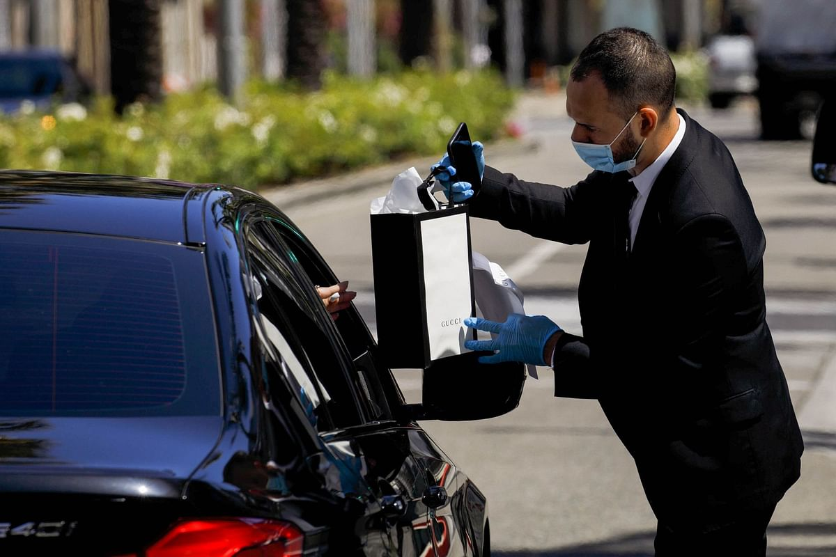 A Gucci employee delivers a purchase to a waiting customer at a pickup location on Rodeo Drive in Beverly Hills, California, on May 19. Photographer: Patrick T. Fallon/Bloomberg