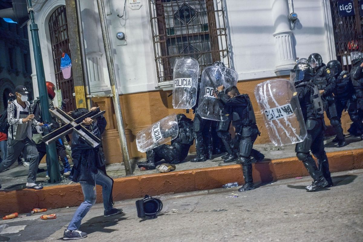 Demonstrators clash with riot police during anti-government protests in Guatemala City's Central Park on Nov. 28. Photographer: Daniele Volpe/Bloomberg